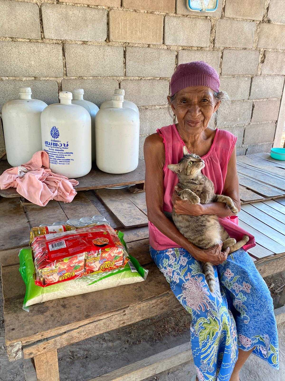 elderly woman with cat and food package